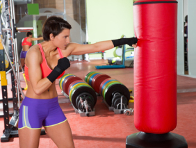 Crossfit woman boxing with red punching bag
